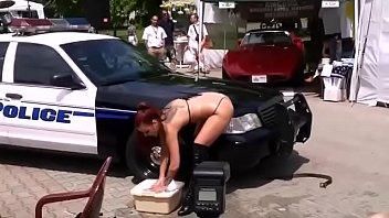 Bikini carwash strip dance near police car